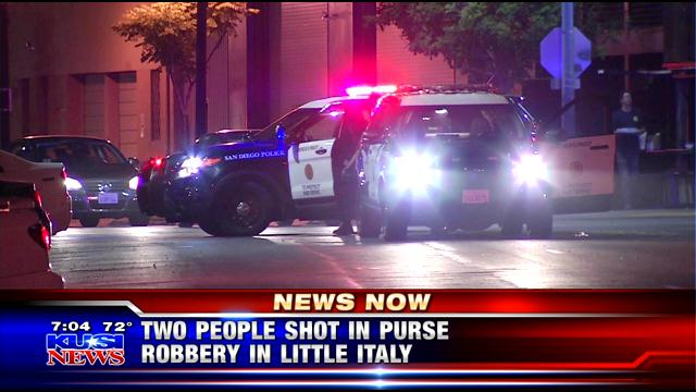 A group of women were robbed at gunpoint in the Little Italy district at night. Two were shot.