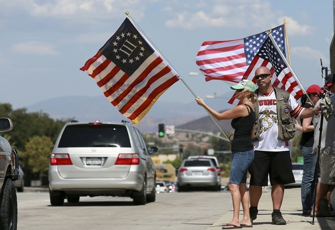 Anti-immigration protesters wave flags at motorists on a highway overpass on Murrieta Hot Springs Blvd in Murrieta, California July 19, 2014. U.S. President Barack Obama will meet with the leaders of Honduras, Guatemala and El Salvador next week to discuss cooperation on the influx of child migrants from Central America into the United States, senior administration officials said on Friday.  REUTERS/Sandy Huffaker  (UNITED STATES - Tags: SOCIETY IMMIGRATION CIVIL UNREST POLITICS) - RTR3ZD1H