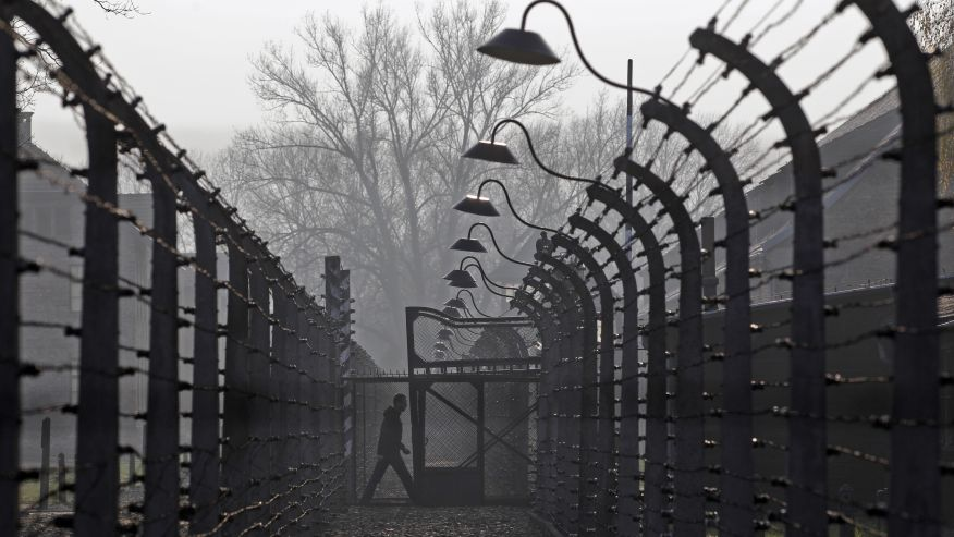 November 18, 2013 - FILE photo of a visitor walking between electric barbed-wired fences at the Auschwitz-Birkenau memorial and former concentration camp . (REUTERS)