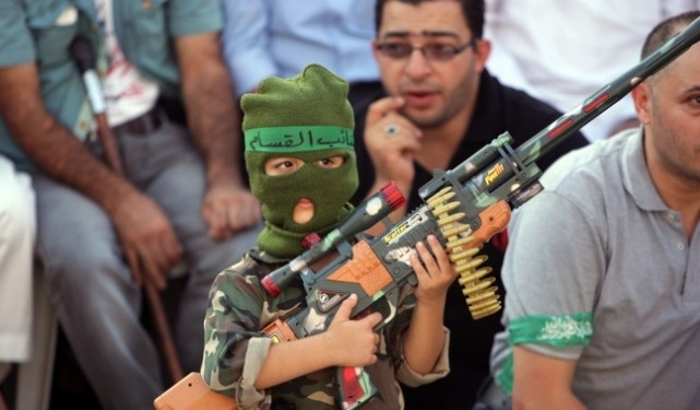 A Palestinian boy holds a toy gun during a celebration organized by Hamas in the West Bank city of Nablus, on Friday, Aug. 29, 2014. (AP Photo/Nasser Ishtayeh)