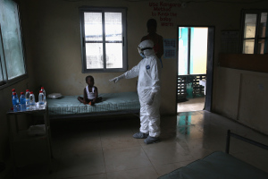 A Liberian Ministry of Health worker, dressed in an anti-contamination suit, speaks to Banu, 4, in a holding center for suspected Ebola patients at Redemption Hospital on October 3, 2014 in Monrovia, Liberia.