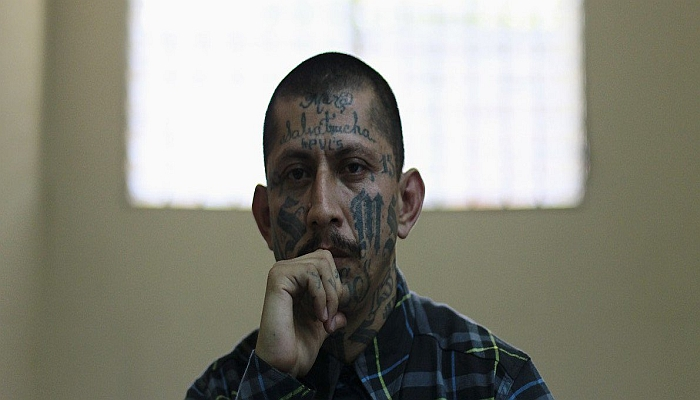 Carlos Tiberio, an imprisoned leader of the Mara MS, listens during a news conference at the high security San Vicente prison in San Vicente April 5, 2013.