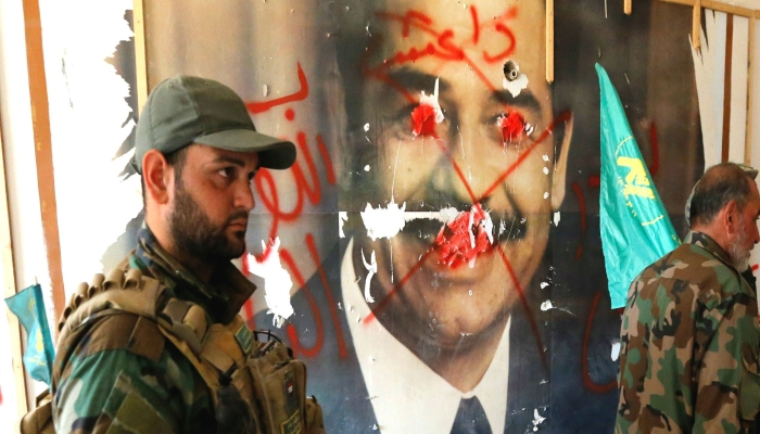 Fighters from the Iraqi Shi'ite Badr Organization walk past a poster depicting images of former Iraqi President Saddam Hussein on the outskirts of Falluja, Iraq, May 28, 2016. REUTERS/Thaier Al-Sudani
