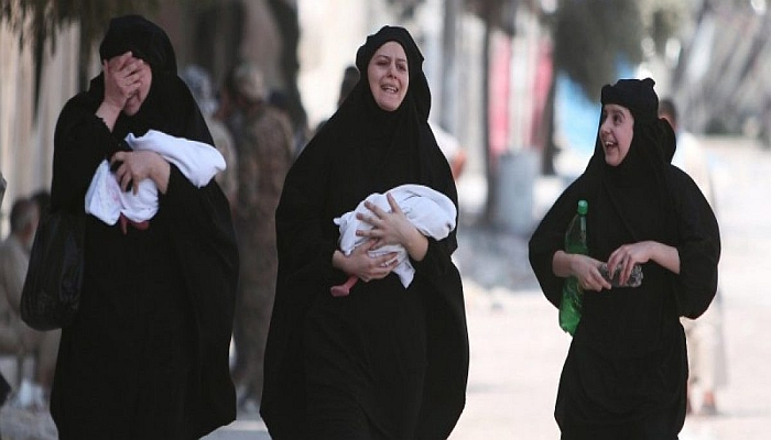 Women carry newborn babies while reacting after they were evacuated by the Syria Democratic Forces (SDF) fighters from an Islamic State-controlled