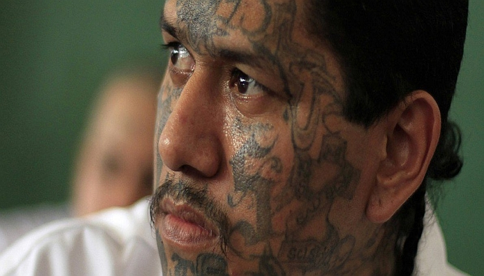 Walter Geovani Salguero, 30, an inmate and member of El Salvador's Mara Salvatrucha (MS-13) gang, participates in a pledge event during a news conference at the Sonsonate jail, outside San Salvador February 8, 2013. The event, sponsored by the country's Catholic Church, involves representatives of the country's two most powerful gangs MS-13 and the 18th Street gang (Mara 18), who pledge not to commit violent acts in various municipalities of the country. It was held in conjunction with the church, civic organizations and government officials, marking the second phase of a truce between the two gangs which was originally signed in March 2012 in an effort to reduce violent crimes in the country. according to the pact's negotiators. Sonsonate is the second most violent city in El Salvador. Picture taken on February 8, 2013. REUTERS/Ulises Rodriguez
