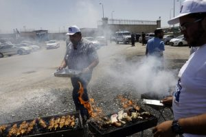 Israeli right-wing activists barbecue outside the Israeli-run Ofer military prison, north of Jerusalem, in the occupied West Bank, on April 20, 2017, where a number of Palestinian prisoners are on a hunger strike. Some 1,500 Palestinian prisoners have joined the hunger strike that began earlier this week, according to Issa Qaraqe, head of detainees' affairs for the Palestinian Authority. / AFP PHOTO / MENAHEM KAHANA