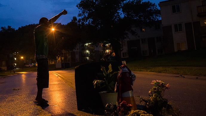 A local resident stands with his arm up over a makeshift memorial at the site where unarmed teen Michael Brown was shot dead in Ferguson, Missouri August 27, 2014 (Reuters / Adrees Latif)