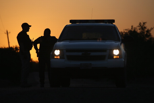 LA JOYA, TX - APRIL 11:  U.S. Border Patrol agents and a pilot from the U.S. Office of Air and Marine (OAM), stop to talk at sunset on April 11, 2013 in La Joya, Texas. In the last month the Border Patrol's Rio Grande Valley sector has seen a spike in the number of immigrants crossing the river from Mexico into Texas. With more apprehensions, they have struggled to deal with overcrowding while undocumented immigrants are processed for deportation. According to the Border Patrol, undocumented immigrant crossings have increased more than 50 percent in Texas' Rio Grande Valley sector in the last year. Border Patrol agents say they have also seen an additional surge in immigrant traffic since immigration reform negotiations began this year in Washington D.C. Proposed reforms could provide a path to citizenship for many of the estimated 11 million undocumented workers living in the United States.  (Photo by John Moore/Getty Images)