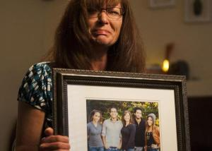 This photo, taken, Friday, Sept. 12, 2014, shows Susan Hunt holding a photo of her family, including her son, Darrien Hunt, at her home in Saratoga Springs, Utah. (Image source: AP/Deseret News, Michelle Tessier)