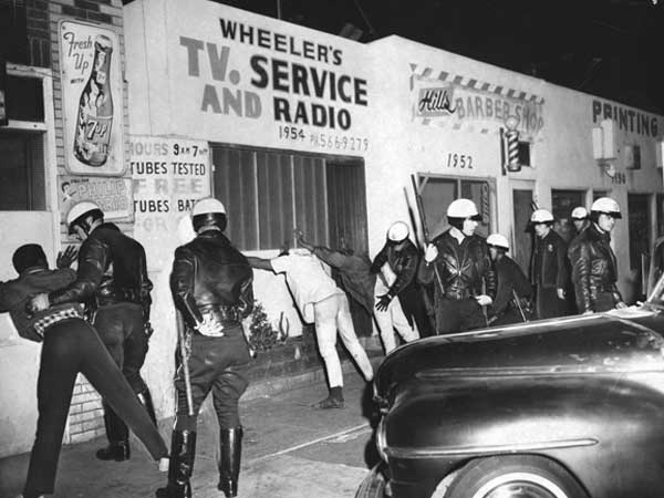 Search for Weapons, Watts Riots (1966): Well armed Police search for weapons in the 1900 block of East 103rd Street in Watts. Police patrolling the riot area stopped boys who were driving around late at night and then released them when no weapons were found. Photograph dated March 16, 1966.