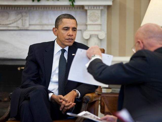 President Barack Obama studies a document held by Director of National Intelligence James Clapper during the Presidential Daily Briefing in the Oval Office, Feb. 3, 2011. (Official White House Photo by Pete Souza) This official White House photograph is being made available only for publication by news organizations and/or for personal use printing by the subject(s) of the photograph. The photograph may not be manipulated in any way and may not be used in commercial or political materials, advertisements, emails, products, promotions that in any way suggests approval or endorsement of the President, the First Family, or the White House.