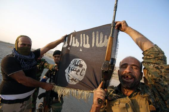 Iraqi Shiite militia fighters hold the Islamic State flag as they celebrate after breaking the siege of Amerli by Islamic State militants, September 1, 2014.