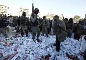 ISIS fighters hold their weapons as they stand on confiscated cigarettes before setting them on fire in the city of Raqqa,April 2, 2014. REUTERS/Stringer