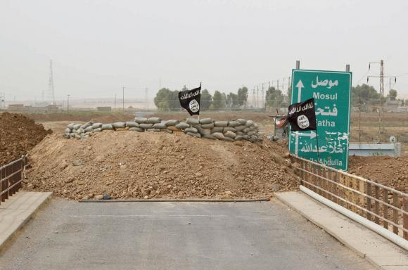 Islamic State flags flutter on the Mullah Abdullah bridge in southern Kirkuk September 29, 2014. CREDIT: REUTERS/AKO RASHEED
