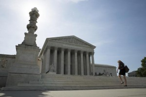 A woman walks to the Supreme Court in Washington in this June 19, 2014 file photo. CREDIT: REUTERS/JOSHUA ROBERTS/FILES