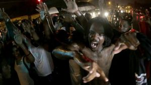 Aug. 17, 2104: People defy a curfew before smoke and tear gas was fired to disperse a crowd protesting the shooting of teenager Michael Brown in Ferguson, Mo. (AP Photo/Charlie Riedel, File)