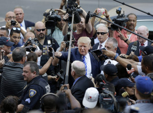 Donald Trump, center, gives a fist bump to a pedestrian as he arrives for jury duty in New York, Monday, Aug. 17, 2015. Trump was due to report for jury duty Monday in Manhattan. The front-runner said last week before a rally in New Hampshire that he would willingly take a break from the campaign trail to answer the summons. (AP Photo/Seth Wenig)