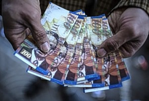 A Palestinian man displays his money after withdrawing it from an automated teller machine (ATM) of the Bank of Palestine in Gaza City on February 5, 2016.By Wissam Nassar.