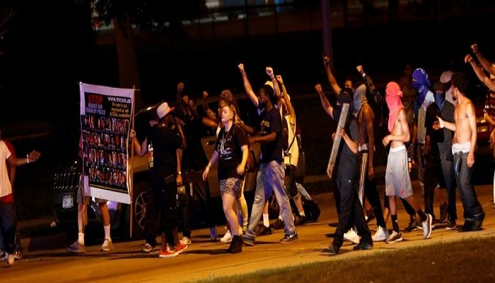 Protestors march toward police lines during disturbances following the police shooting of a man in Milwaukee, Wisconsin. REUTERS/Aaron P. Bernstein
