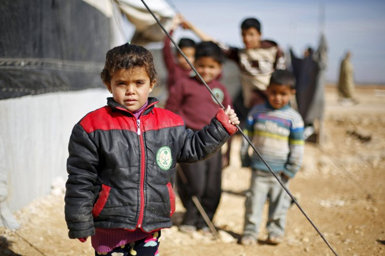 Syrian refugee children pose as they play near their families' residence at Al Zaatari refugee camp in the Jordanian city of Mafraq, near the border with Syria, January 30, 2016. REUTERS/ Muhammad Hamed