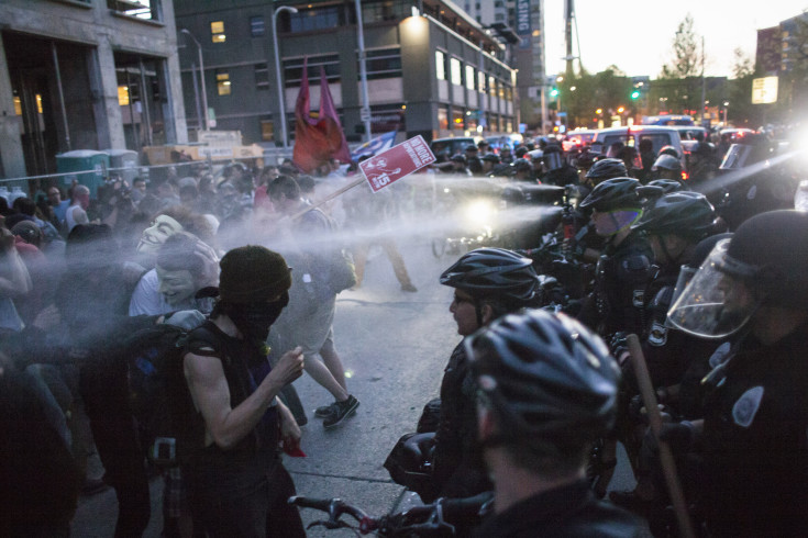 Policemen target protestors with pepper spray during an anti-capitalist demonstration in Seattle, Washington May 1, 2014. Hundreds marched through the streets, with intermittent violence and several arrests made. REUTERS/David Ryder   (UNITED STATES - Tags: BUSINESS EMPLOYMENT CIVIL UNREST) - RTR3NH97
