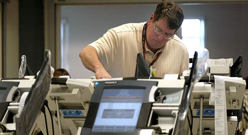 ** FILE **  An election worker downloads votes from an electronic voting machine, at the Cuyahoga County Board of Elections in Cleveland in this May 3, 2006 file photo. A review panel is asking voters and election workers what went wrong in the botched primary as it tries to improve Cuyahoga County's elections. The public input is part of an ambitious plan by the panel, which is facing a tight deadline to report back to the elections board. (AP Photo/Jamie-Andrea Yanak)